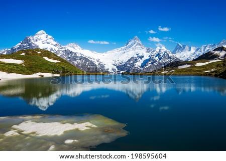 Wetterhorn, Schreckhorn, and Finsteraarhorn peaks reflected in the waters of the Bachalpsee lake, Swiss Alps. - stock photo