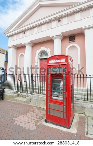 WEYMOUTH, UK - JUNE 13: Vintage red telephone box converted into a ATM cash machine in Weymouth, UK - June 13, 2013 - stock photo