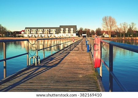 Wharf scaffold above  sea at harbor. Big house on coast, smooth water level - stock photo