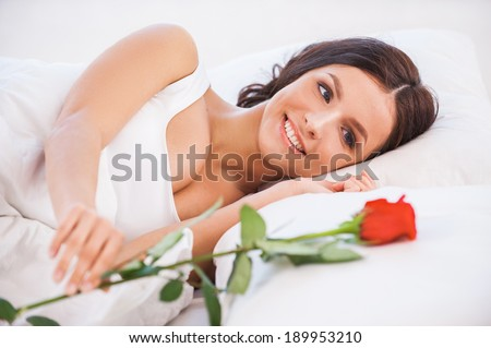 What a beautiful morning. Side view of beautiful young woman lying in bed with red rose   - stock photo