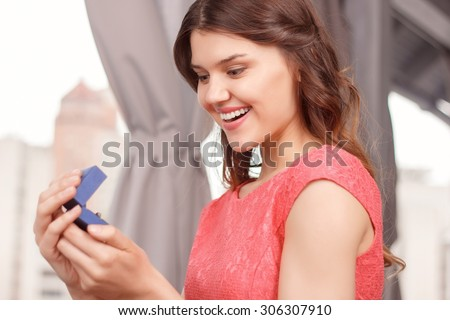 What a beauty. Portrait of young attractive happy woman holding ring case in restaurant.