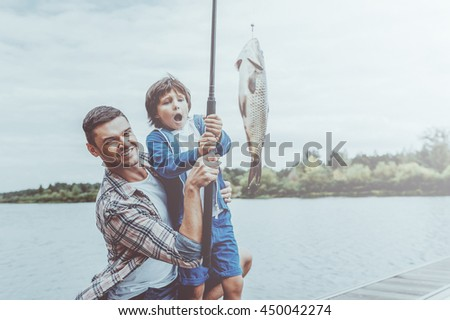 What a fish! Father and son stretching a fishing rod with fish on the hook while little boy looking excited and keeping mouth open - stock photo