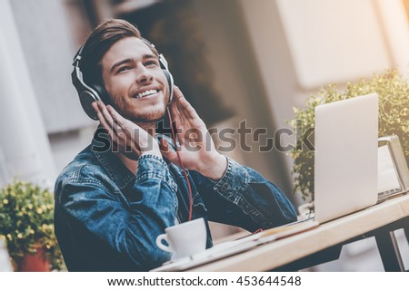 What a great day! Cheerful young man holding hands on headphones while sitting at sidewalk cafe - stock photo