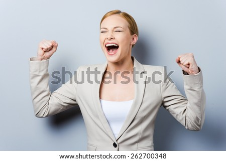 What a lucky day! Happy young businesswoman keeping arms raised while standing against grey background - stock photo