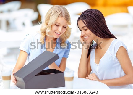 What a nice bargain . Pleasant cheerful charming girls sitting at the table and opening the box while expressing positivity.