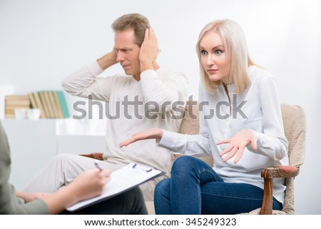 What a problem. Adult couple  sitting on the sofa and disputing while talking with psychologist  during psychological therapy session
