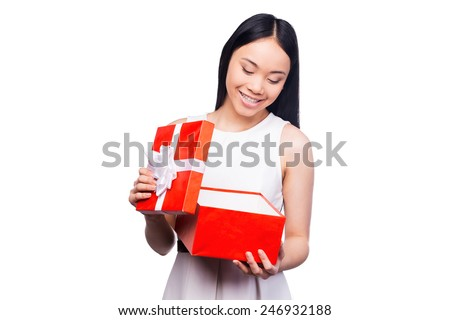 What a surprise! Beautiful young Asian woman opening gift box and looking inside with smile while standing against white background