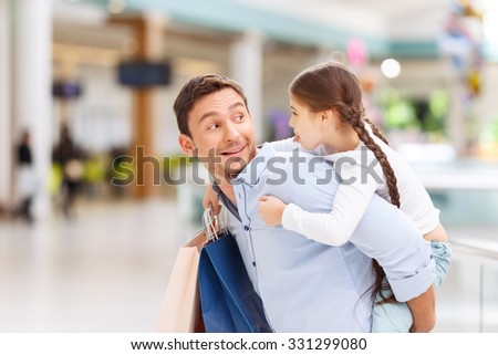 What a surprise. Cheerful joyful father holding his daughter on the back while having shopping in a  mall - stock photo