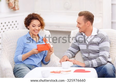 What a surprise. Nice contented emotional girl opening present and showing wonder while sitting at the table with her boyfriend - stock photo