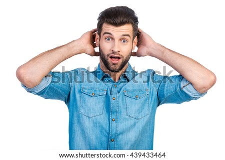 What a surprise! Surprised young handsome man in jeans shirt holding hands behind head and keeping mouth open while standing against white background  - stock photo
