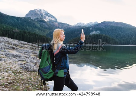 What a view.  Shot of a young woman taking  pictures on her smartphone while hiking - stock photo