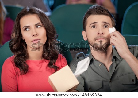 What a wonderful movie! Cheerful young couple watching movie at the cinema - stock photo