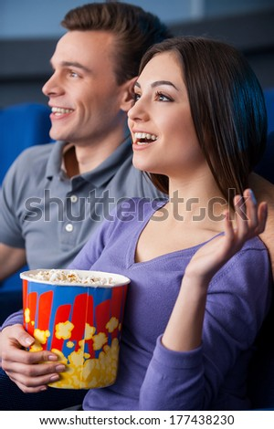 What an exciting movie! Side view of happy young couple eating popcorn while watching movie at the cinema  - stock photo