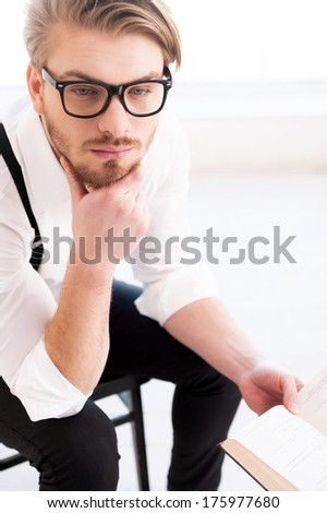 What an interesting fact! Top view of thoughtful young man in shirt and suspenders holding a book and looking away while sitting on the chair - stock photo