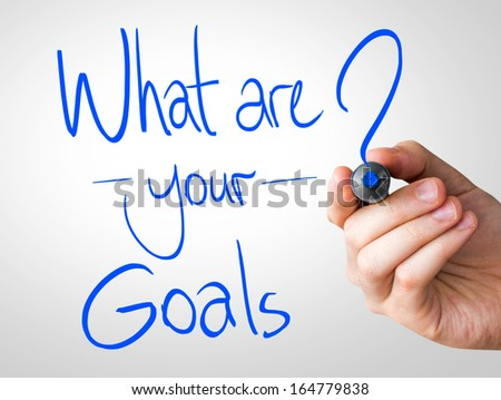What are your goals hand writing with a blue mark on a transparent board - stock photo
