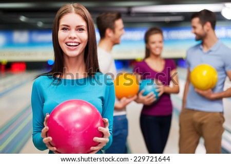 What can be better than bowling? Beautiful young women holding a bowling ball while three people communicating against bowling alleys  - stock photo