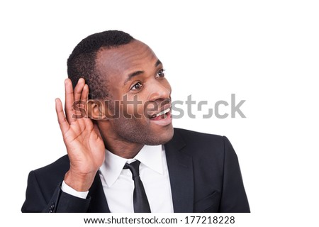 What did you say? Cheerful young African man in formalwear holding hand near ear and smiling while standing isolated on white background  - stock photo