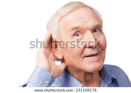 What did you say? Handsome senior man holding hand near his ear and smiling while standing against white background - stock photo