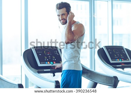What did you say? Rear view of young handsome man in sportswear standing on treadmill in front of window at gym and adjusting his headphone while looking at camera with smile - stock photo