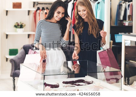 What do you think about this? Two beautiful women with shopping bags looking at lingerie showcase with smile while standing at the store - stock photo