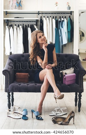 What else do I need? Beautiful young woman looking thoughtful while sitting on sofa at the clothing store - stock photo