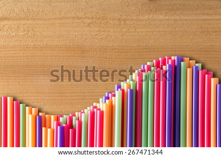 What goes up must come down concept on wood with a wavy line of vivid multicolored drinking straws in an undulating pattern, with copy space - stock photo