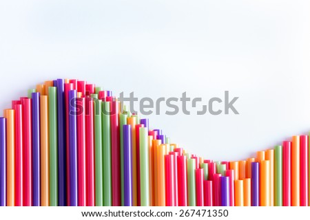 What goes up must come down concept with a wave form arrangement of colorful plastic drinking straws over a light grey background with copy space - stock photo