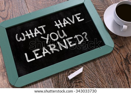 What Have You Learned? Motivational Quote Hand Drawn on Blue Chalkboard on Wooden Table. Business Background. Top View. - stock photo