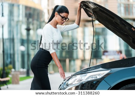 What is the problem here? Side view of confident young businesswoman looking inside of the vehicle hood while standing near her car - stock photo