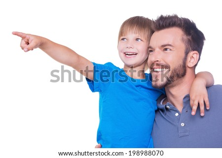 What is there? Side view of happy father and son looking away while child pointing away and both standing isolated on white - stock photo