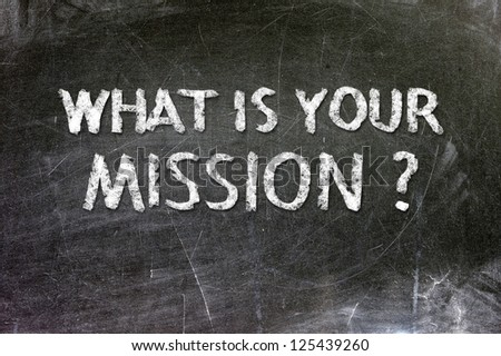 What is your mission handwritten with white chalk on a blackboard. - stock photo