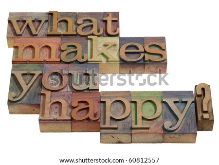 What makes you happy - a question spelled in vintage wooden letterpress printing blocks, isolated on white
