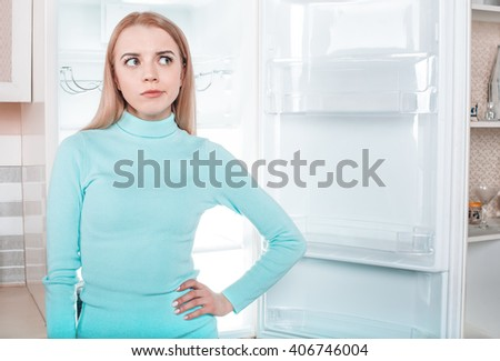 What's for dinner? Pretty blonde standing near open empty fridge. Thoughtful young woman looking aside - stock photo