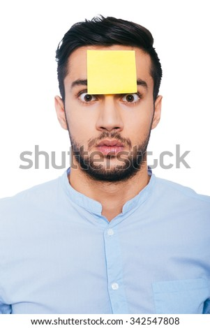 What was that? Shocked young Indian man with adhesive note on his forehead staring at you while standing against white background - stock photo