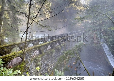 Whatcom Falls Bridge, Bellingham, Washington. Whatcom falls and the historic bridge spanning Whatcom Creek in the misty, morning light. Bellingham, Washington. - stock photo
