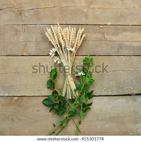 Wheat and daisies  lying on a wooden background