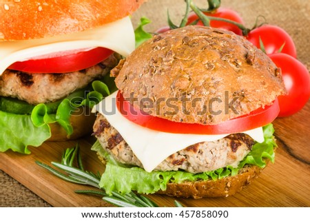 Wheat and rye burgers on wood board with rosemary and tomato. On linen towel