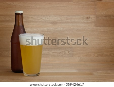 Wheat beer in glass and bottle over wood