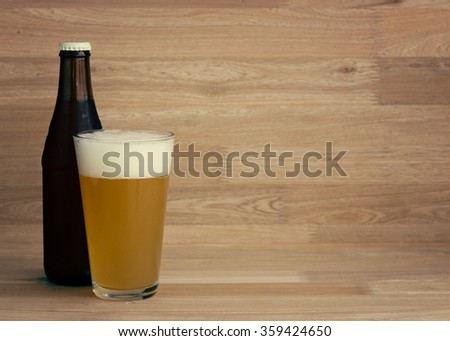 Wheat beer on glass and beer bottle on wood