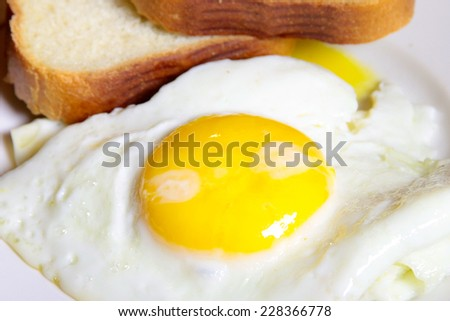 wheat bread and fried eggs as part is morning meal - stock photo