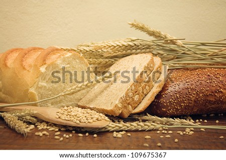 Wheat bread and wheat grain and ears on wooden kitchen table.