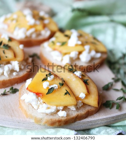 Wheat bread baguette bruschetta with salted greek feta cheese, fresh ripe nectarine slices, thyme and honey drizzling on a cutting board for snack - stock photo