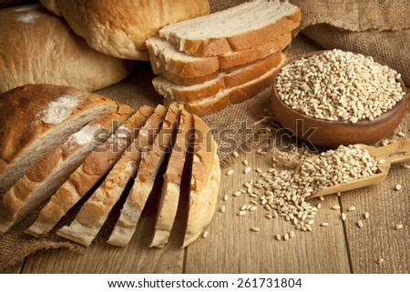 Wheat Bread, wheat seeds and bread slices with wooden background - stock photo
