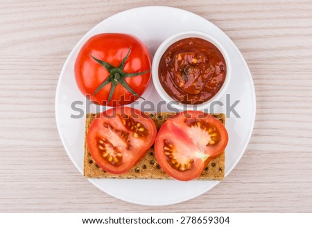 Wheat crisp bread, bowl with ketchup and tomato in white plate on table, top view - stock photo