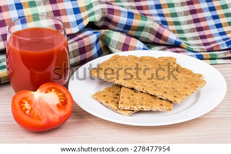 Wheat crisp bread, tomato and juice in glass on wooden table - stock photo