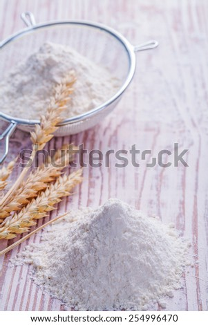 wheat ears an flour in pin on vintage wooden desk  - stock photo