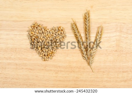 Wheat ears and wheat grian in a heart shape on a wooden board - stock photo