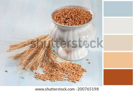 Wheat ears on a wooden background  with complimentary swatches. - stock photo
