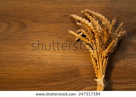 Wheat Ears on the Wooden Table. Sheaf of Wheat over Wood Background. Harvest concept - stock photo