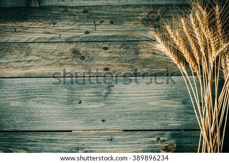 Wheat Ears on the Wooden Table. Sheaf of Wheat over Wood Background. Harvest concept. Vintage style. - stock photo